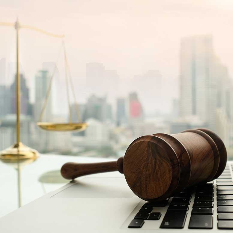Gavel laying on laptop keyboard with scales of justice in background