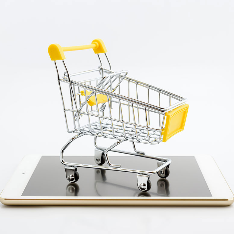 Mini shopping cart with yellow accents on top of iPhone with gold back