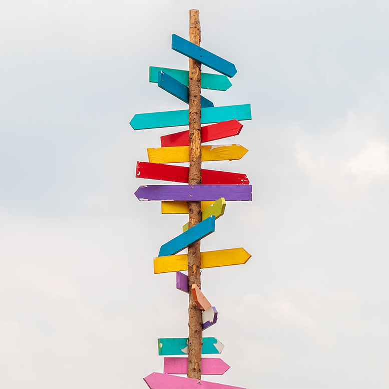 Colorful directional arrows on wooden post