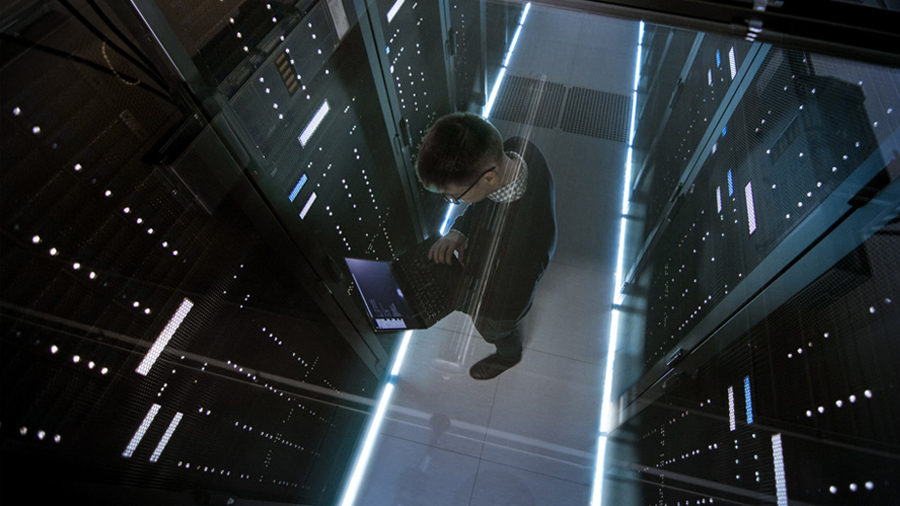 Bird's eye view of man standing in server room holding a laptop and looking at code on the screen