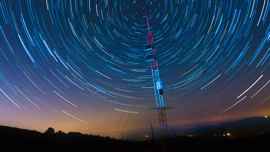 Radio tower surrounded by star trails in night sky